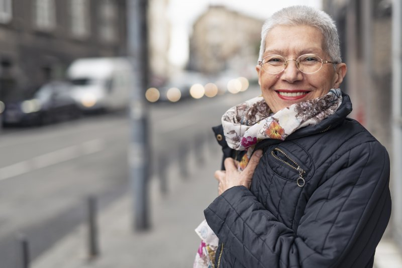 an older woman smiling while bundled up in a coat
