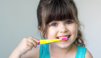 A little girl in a blue shirt brushing her teeth