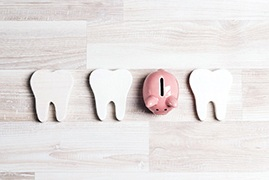 three teeth lined up with a piggy bank filling the gap between the third and second tooth