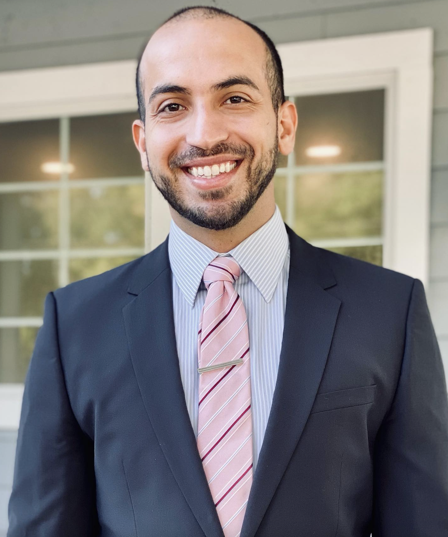 Dentist in a suit with pink striped tie