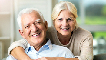 Older couple smiling with single tooth implants in Lake Wales