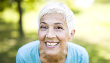 Woman with short hair smiling while outside