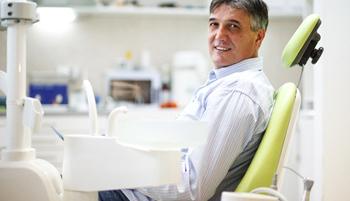 Man looking at camera smiling in dental chair
