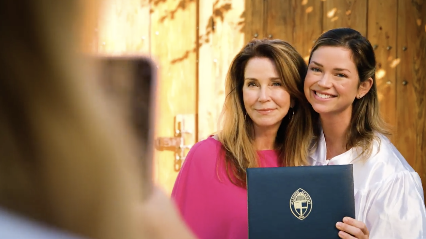 a mom and daughter posing with highschool diploma