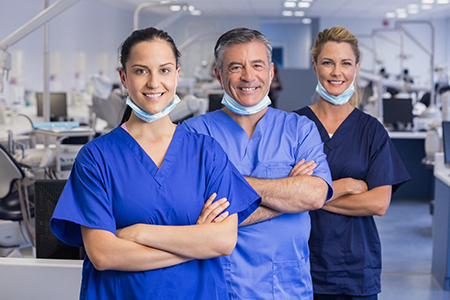 Group of implant dentists in Lake Wales smiling in dental lab.