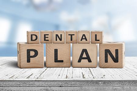 "Wooden blocks spelling out the phrase ""dental plan."""