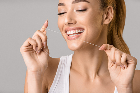 Woman using floss to clean her dental implants in Lake Wales.