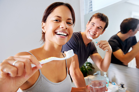 Woman holding toothbrush and smiling with husband.