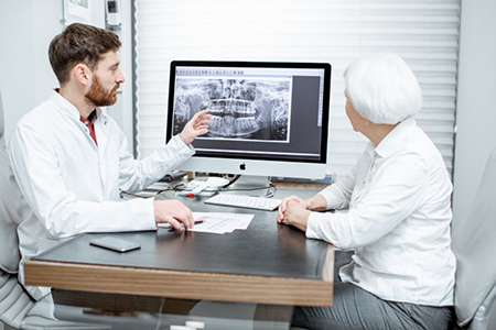 Implant dentist in Lake Wales showing patient an X-ray.